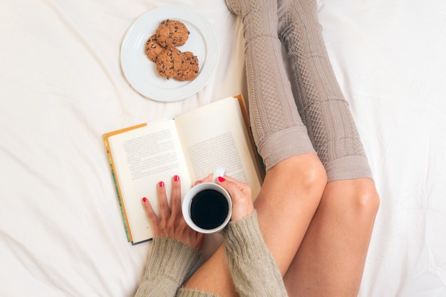 Woman eating breakfast in bed while reading a book