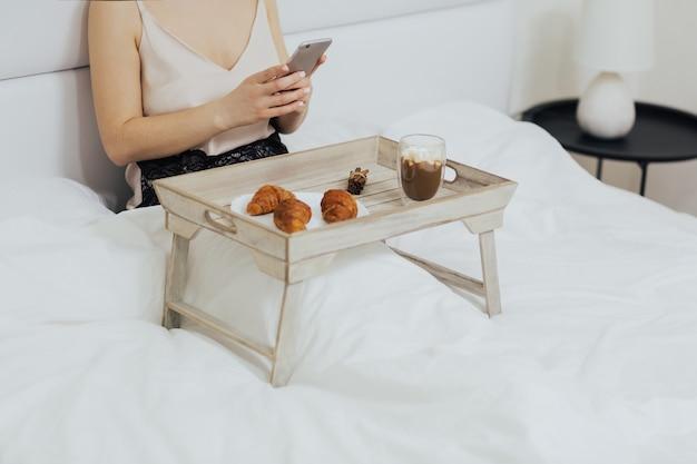ベッドに座っている間、木製のトレイから朝食を食べる女性