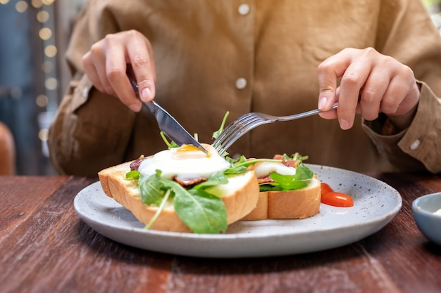 A woman eating breakfast sandwich with eggs, bacon and sour cream by knife and spoon in a plate on wooden table