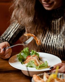 Женщина ест салат цезарь в ресторане