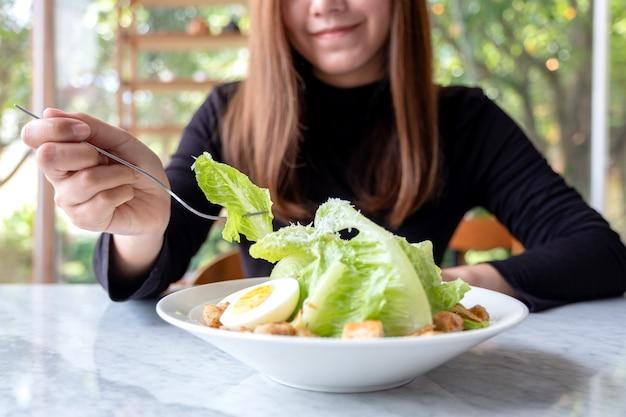 A woman eating caesar salad