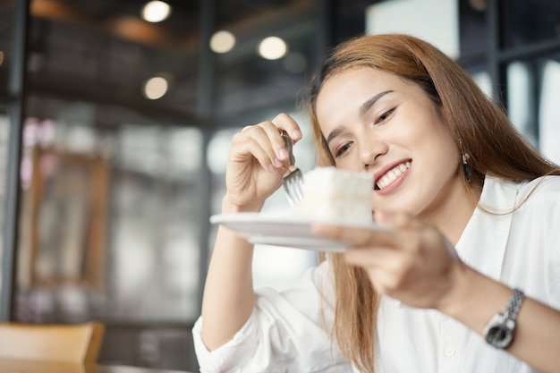 デザートカフェでケーキを食べる女性。