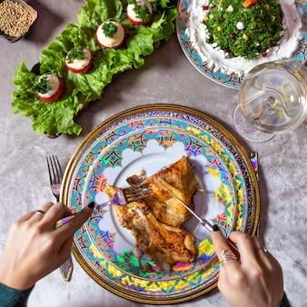 テーブルトップビューで鶏肉を食べる女性