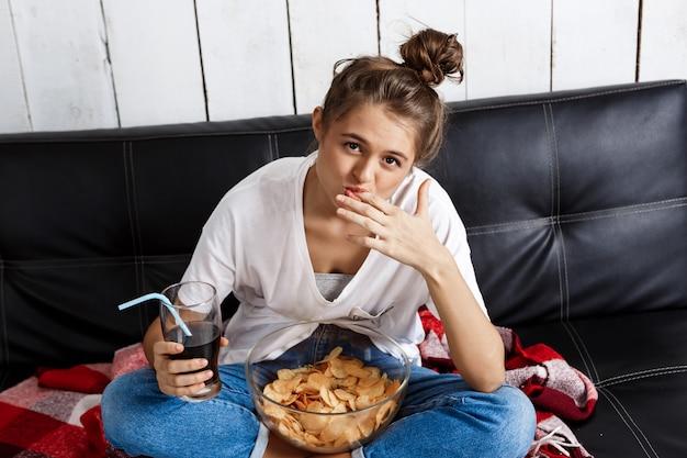 Woman eating chips, drinking soda, watching tv, sitting at sofa.