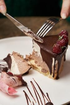 Женщина ест шоколадный торт с малиной. женщина руки резки шоколадный мусс торт с малиной