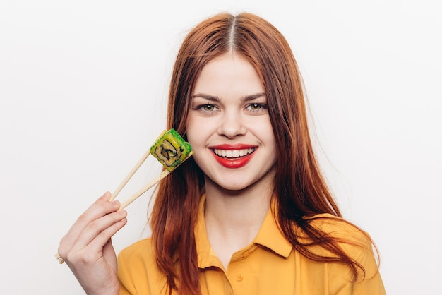 Woman eating colored rolls with bamboo chopsticks