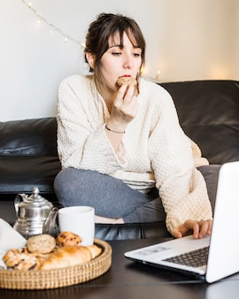 Woman eating cookie while working on laptop