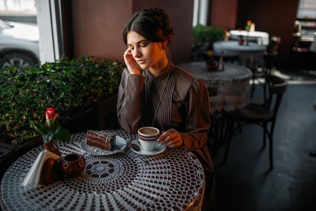 カフェでおいしいチョコレートケーキを食べる女