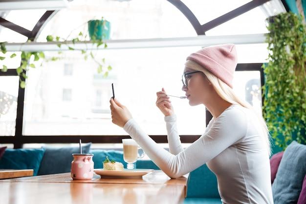 Женщина ест десерт и использует мобильный телефон в кафе