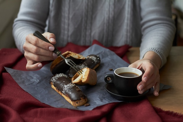 Woman eating eclairs filled with cream, traditional french eclairs with chocolate and cup of espresso.