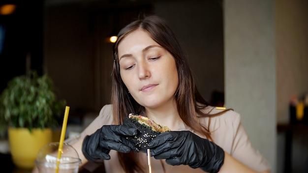 レストランでファーストフードチキンバーガーを食べる女性。