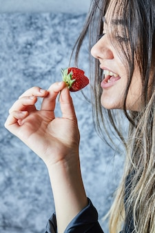 Woman eating fresh red strawberry on marble surface