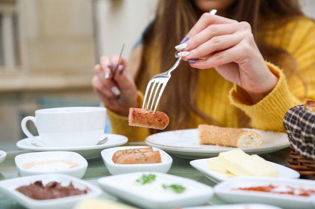 Женщина ест жареные колбаски во время завтрака крупным планом зрения