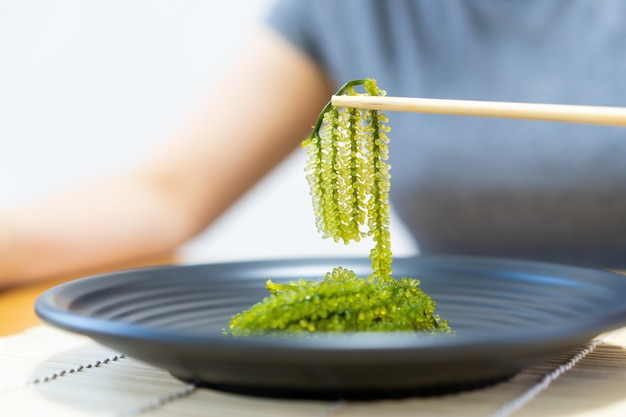 Woman eating a grape seaweed by using wooden chopstocks close up.