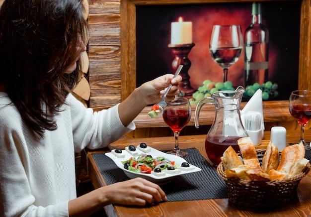 Женщина ест греческий салат с фруктовым соком и хлебом