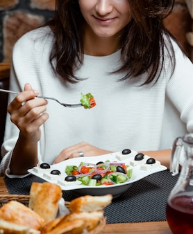 Woman eating greek salad with tomato, onion