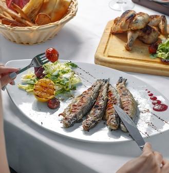 Женщина ест жареную рыбу с салатом, лимоном и помидорами на гриле
