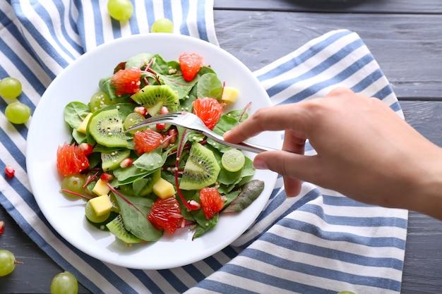 健康的な新鮮なサラダを食べる女性、クローズアップ
