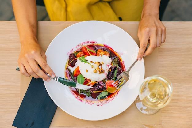 Женщина ест здоровый салат с сыром буррата, рукколой и салатом из свеклы
