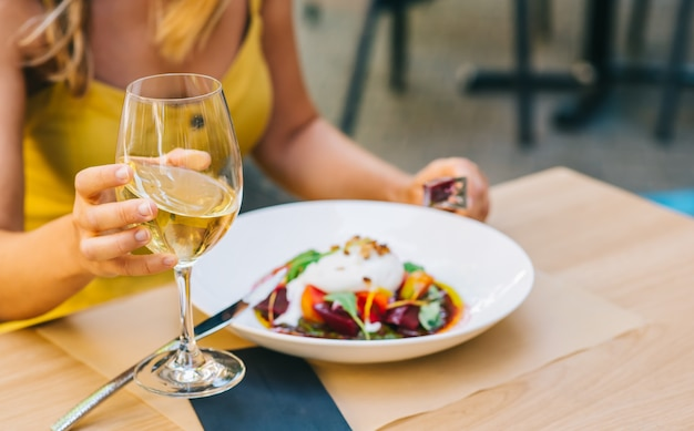 Женщина ест здоровый салат с сыром буррата, салатом из рукколы и помидорами и держит белое вино в стакане