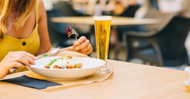 Женщина ест здоровый салат с сыром буррата, салатом из рукколы и помидорами