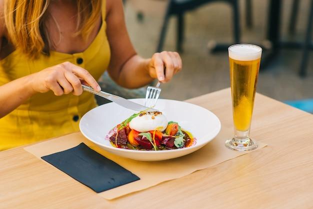 Женщина ест здоровый салат с сыром буррата, салат из рукколы