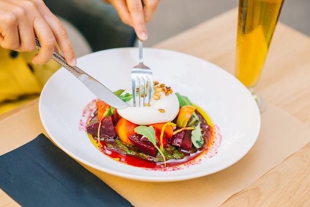 Женщина ест здоровый салат с сыром буррата