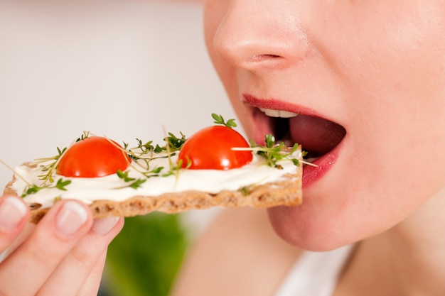 Woman eating a healthy toast with tomato and cheese
