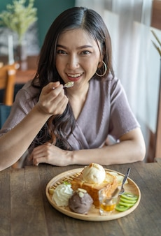 Woman eating honey toast, sweet dessert in cafe