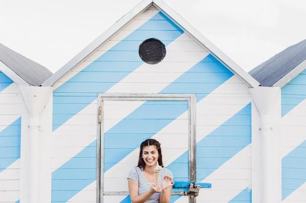 ビーチで木製家の前でアイスクリームを食べる女性