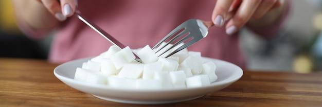 テーブルのクローズアップでナイフとフォークで皿から砂糖の塊を食べる女性。糖尿病の概念が発展した理由