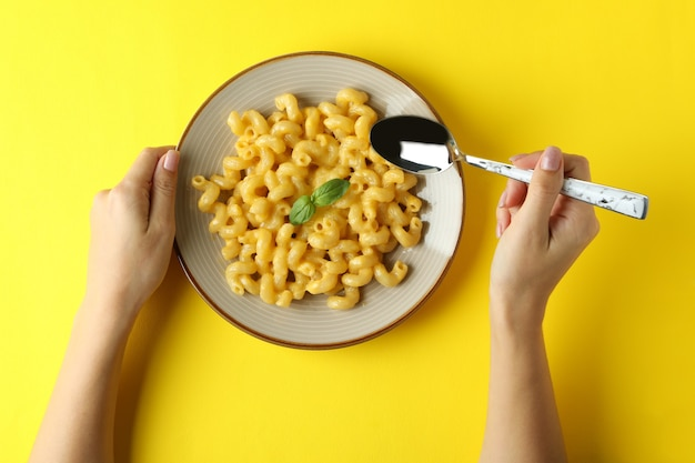 Woman eating macaroni with cheese on yellow background, top view