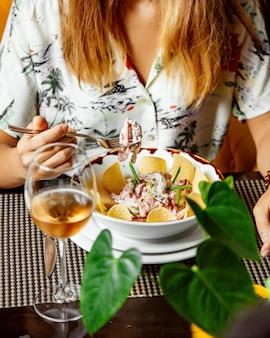 La donna che mangia l'insalata della carne con le fette di julienne del pomodoro è servito con le patatine fritte
