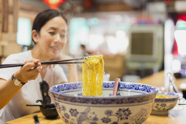 Woman eating noodles soup in big bowl with chopsticks.