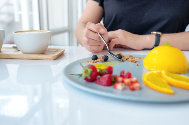 A woman eating orange cake with mixed fruit by spoon in cafe
