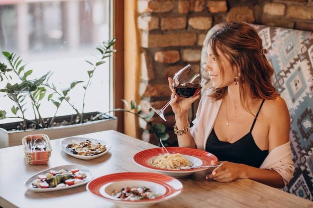 Женщина ест пасту в итальянском ресторане