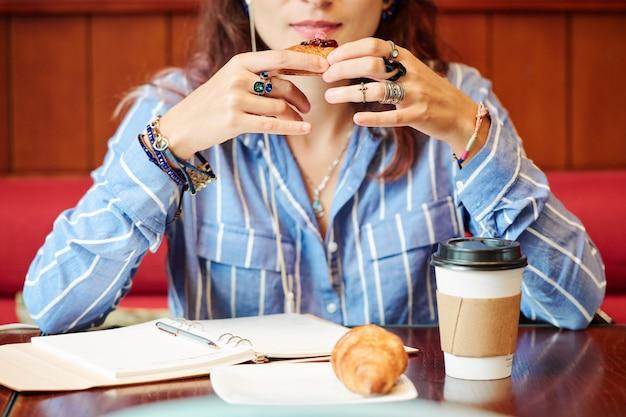 Женщина ест выпечку с кофе