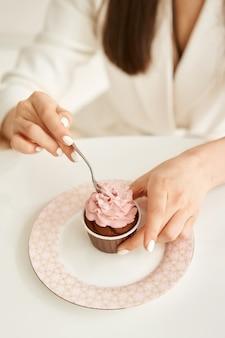 Женщина ест розовый кекс на тарелке с маленькой ложкой