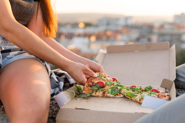 Woman eating pizza outdoors
