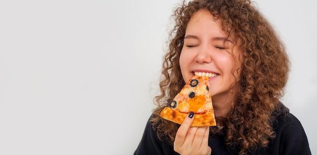 ピザを食べる女性、白い背景にピザのスライス、コピースペースを持つ女性の肖像画。フードデリバリーのコンセプト。