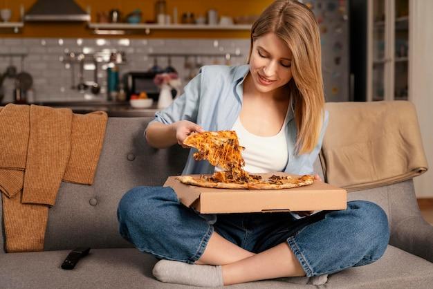 テレビを見ながらピザを食べる女性