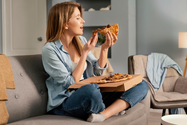 Woman eating pizza while watching tv