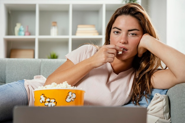 Женщина ест попкорн, глядя на ноутбук
