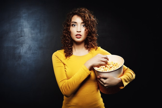 ロードショーで映画を見ながらポップコーンを食べる女性