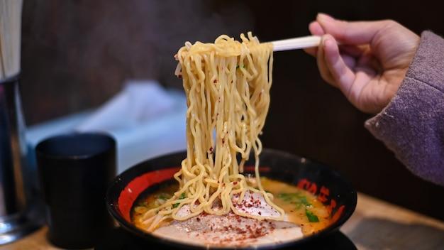 Woman eating ramen with chopsticks