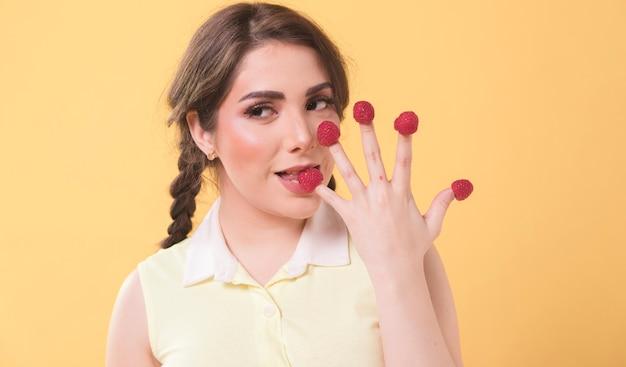 Donna che mangia i lamponi fuori dalle sue dita