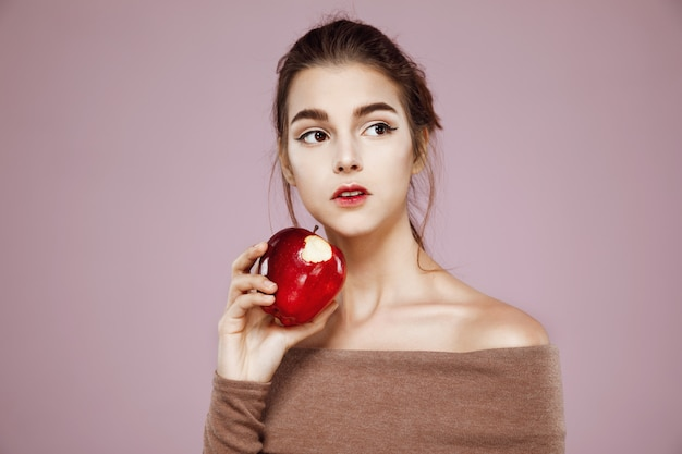Woman eating red apple looking in side on pink