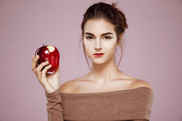 Woman eating red apple on pink