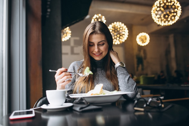 Woman eating salad in a cafe