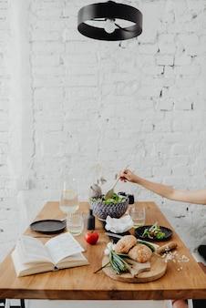Женщина ест салат на кухне